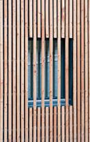 Lärchenfassade verdeckt geschraubt auf Hinterlüftung mit schwarzem Vlies.
